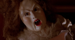 evil killer doll with fangs from horror film Dolls (1987)